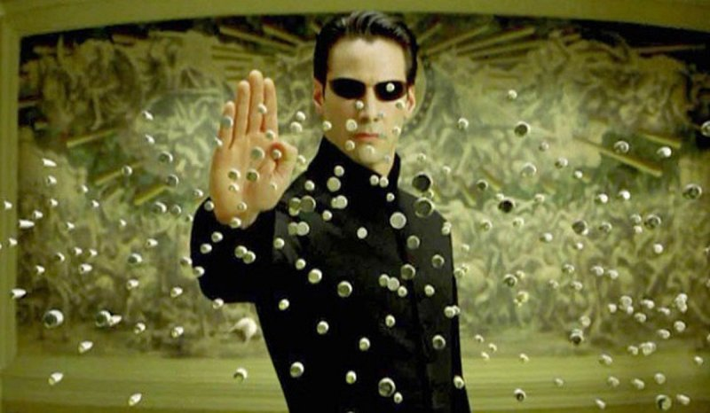 This image is from the film The Matrix. Neo, wearing a black coat and glasses, stops an amass of bullets with his hand.