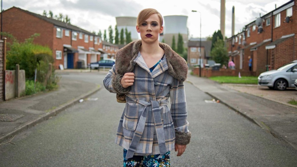The image is from the film Slap. Connor walks in the middle of a street, wearing a dress and make-up in the full light of day.