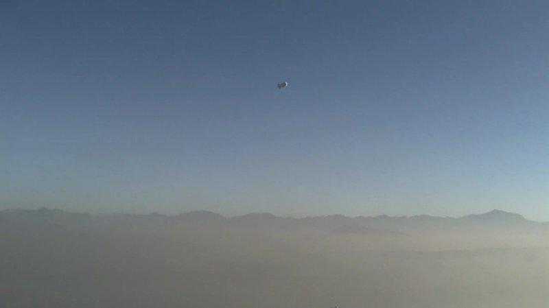 A zeppelin-like balloon flies above a dusty Afghanistan.