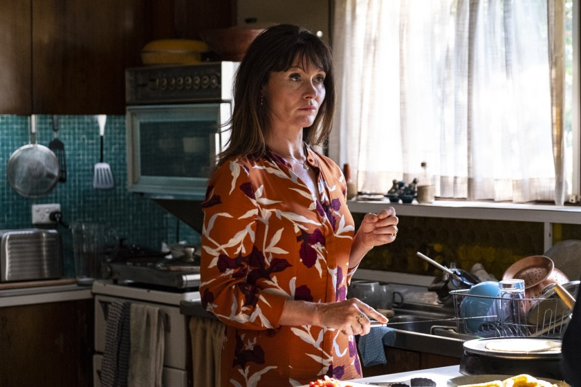 The image is from the film Babyteeth. A woman in a orange floral dress stands in the kitchen.