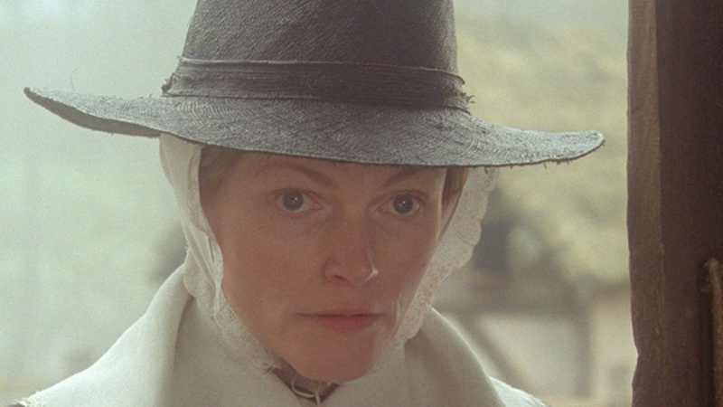 Maxine Peake in Fanny Lye Deliver'd. A middle-aged woman with blue eyes, dressed in 17th century Puritan clothing, stands in a doorway and stares ahead.