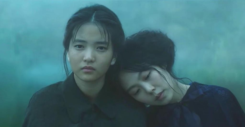 Hideko lays her head on Sook-Hee's shoulder. Both are dressed in black.