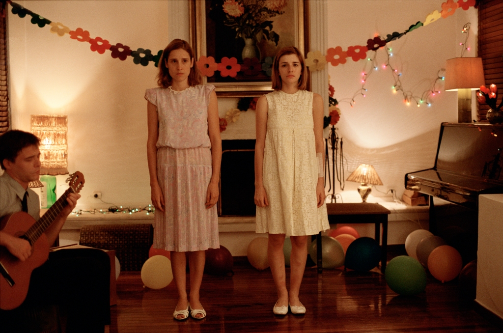 Still from 'Dogtooth'. Features two girls stood quite rigidly, looking unhappy. A man on the left sits and plays guitar. There are party decorations in the room.