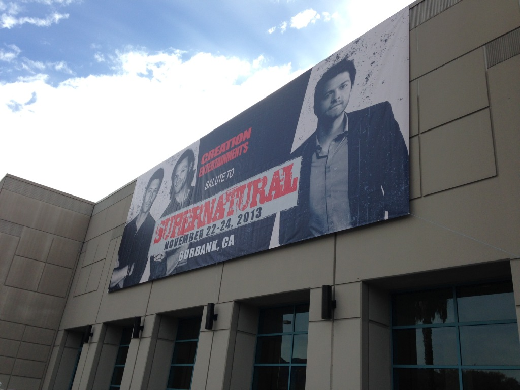 "Image of Supernatural convention banner. The banner reads ""Creation Entertainments Salute to Supernatural November 22-24, 2013 Burbank, CA."" In the banner is Jensen Ackles, Jared Padalecki and Misha Collins"
