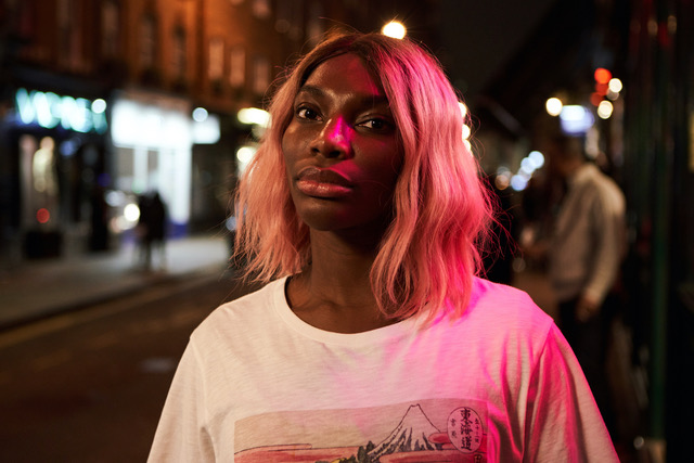 The image is from the TV Show I May Destroy You? A woman stands in a high street late at night. She has pink hair..