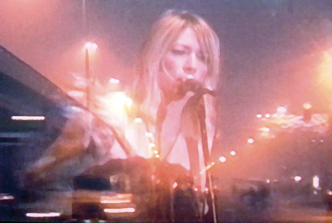 Image shows singer Kim Gordon performing, overlayed is the image of a motorway at night.