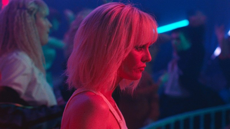 This image is from the film Knife + Heart. A woman stands in the middle of the image, with a red light covering her. She is in a nightclub, which is entirely blue.