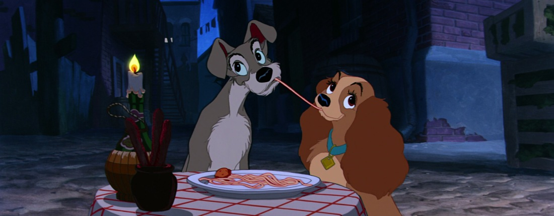 Two dogs, a scruffy grey mutt and a golden brown cocker spaniel, share a plate of spaghetti at a small round table in a back alley. A single strand of spaghetti that they are both eating connects them.