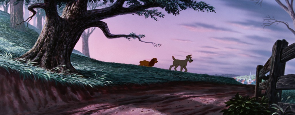 Two dogs, a golden brown cocker spaniel and scruffy grey mutt, make their way down a grassy hill. The environment is prominent and the dogs small and far away. A sunrise tints the image with purple hues.