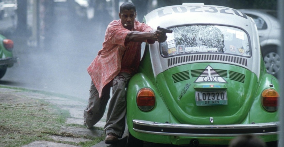 Tony Scott's Man on Fire. Denzel Washington leans against a green Volkswagen Beetle, aiming a gun off-camera.