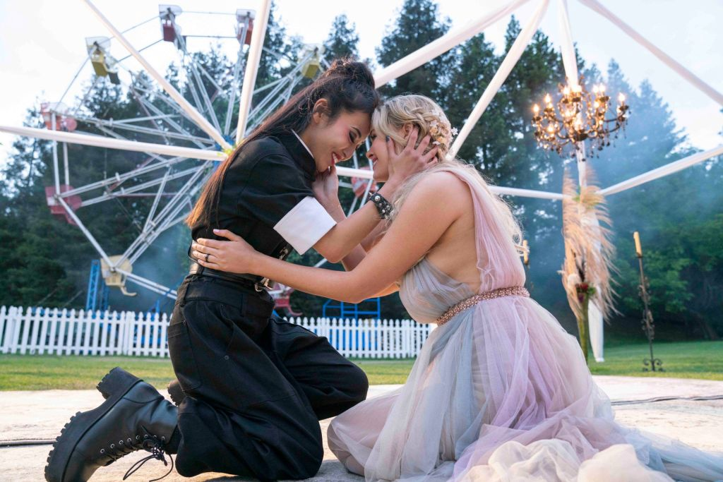Karolina and Nico hold one another in am embrace at a fairground. Nico is dressed all in black whilst Karolina wears a pastel coloured dress.