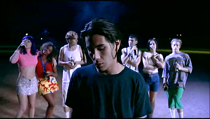 Image is from the film Nowhere (1997). A man looks down in the center of the shot. A series of teenagers stand behind him drinking beer.