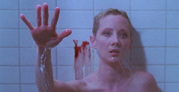 Marion is in the shower. There is blood on the wall behind her. She is holding our her hand.
