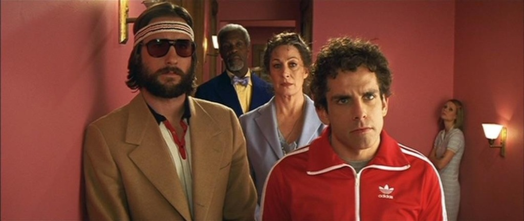 Screencapture from The Royal Tenenbaums. 5 people stand in a hallway.