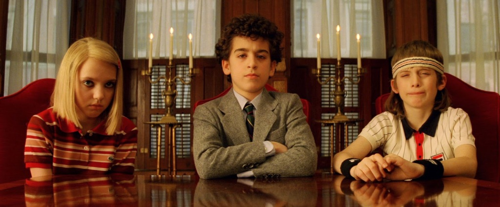 Screengrab from The Royal Tenenbaums. 3 children, 2 male and 1 female, sit at a table.
