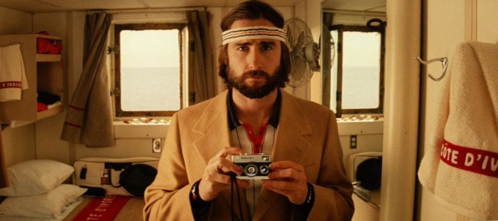 Screencapture from The Royal Tenenbaums. A man in a ship cabin holds up a camera.