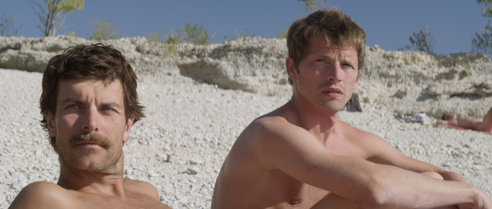 Stranger by the Lake - Michel (Christophe Paou) and Franck (Pierre Deladonchamps) sit naked on the lakeside in the sun.