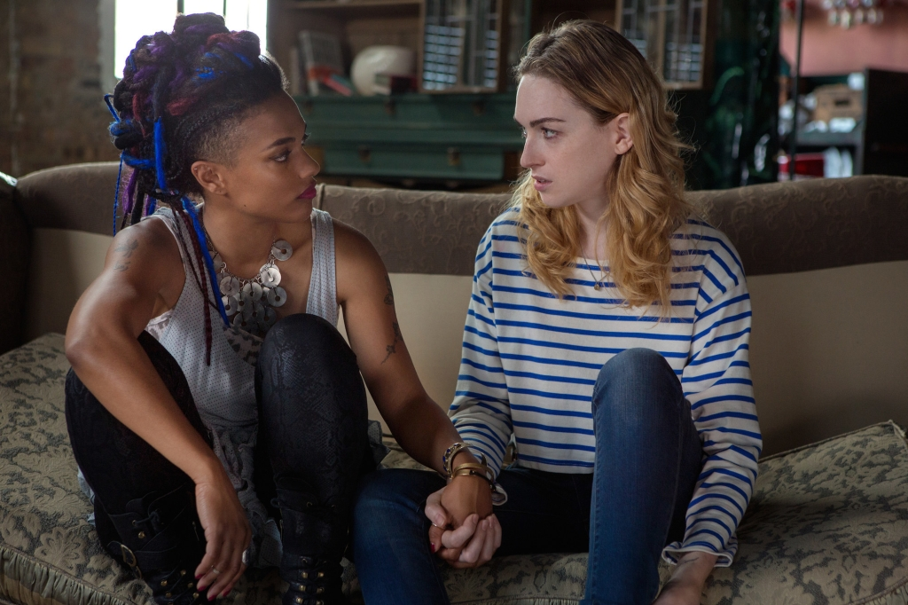 Nomi and Amanita are holding hands. Nomi is a blonde woman wearing a navy striped top. Amanita has colourful dreadlocks and has multiple tattosos.