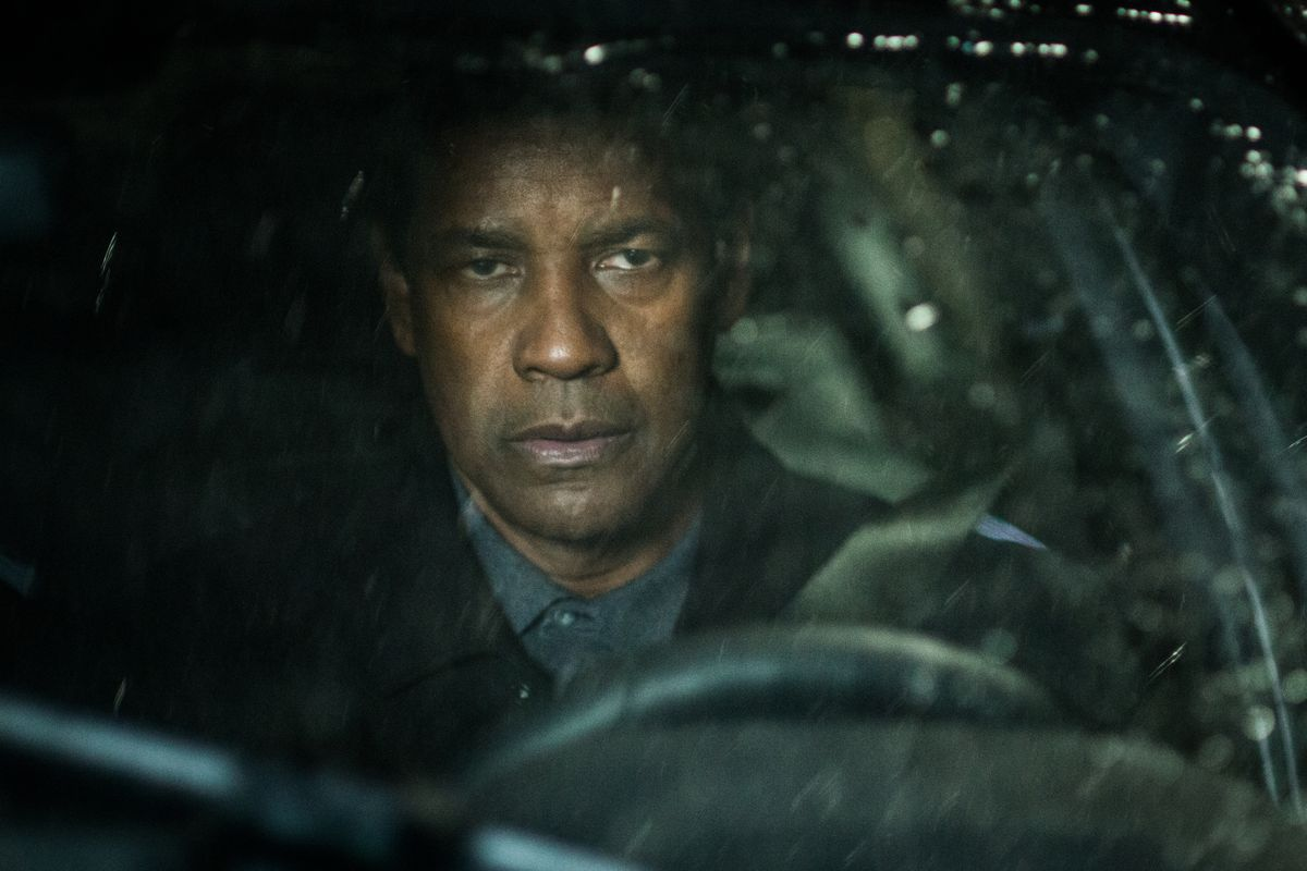 The Equalizer. Denzel Washington sits in the driving seat of a car in the night-time, glowering off-camera.