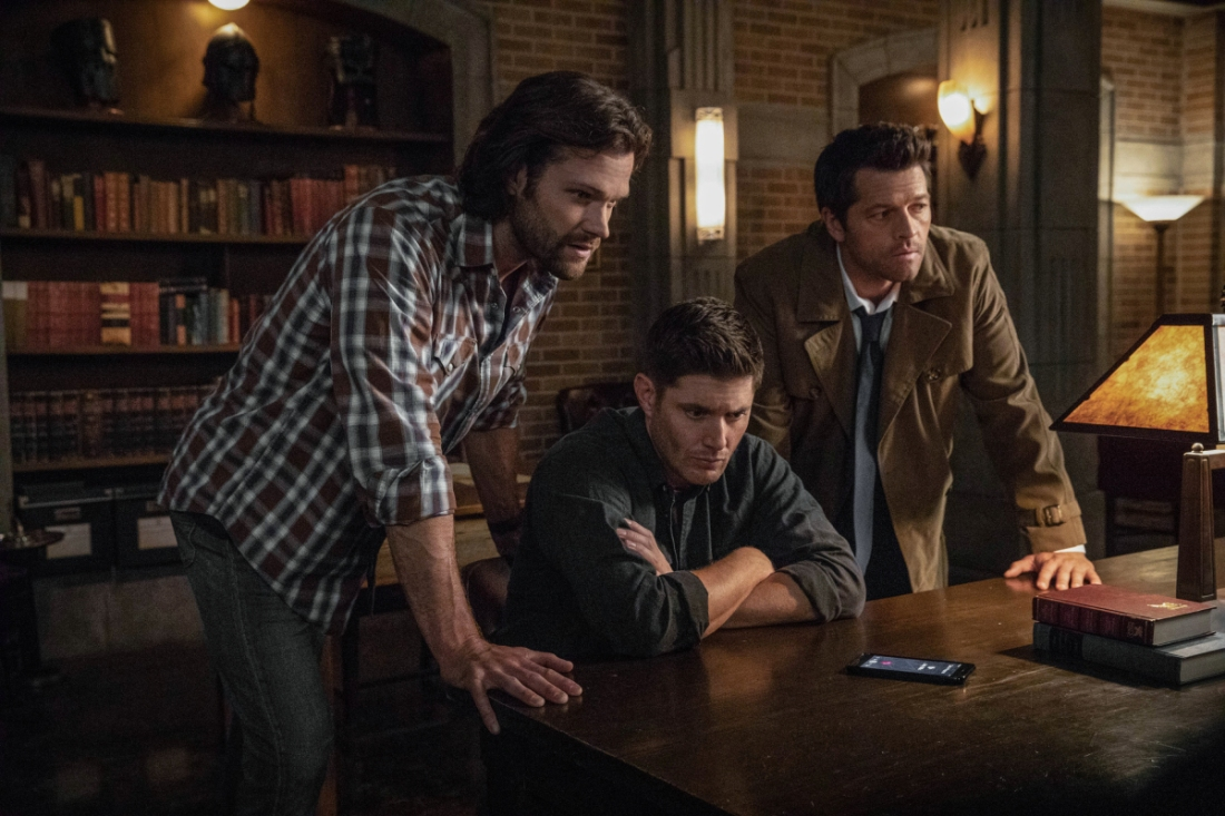 Image of Sam Winchester, Dean Winchester and Castiel. They are standing around a table