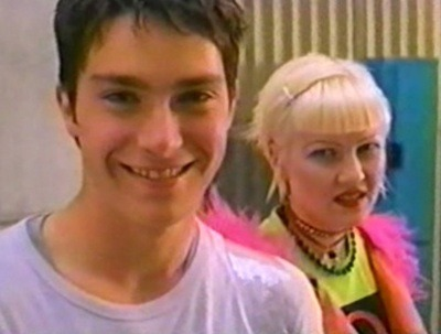 This image is from This is How the World Ends. A teenage boy smiles at the screen. Behind him, a blonde girl sneers.