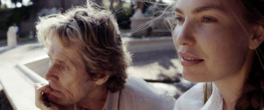 Close-up image of Willem Dafoe and Cristina Chiriac looking to the side.