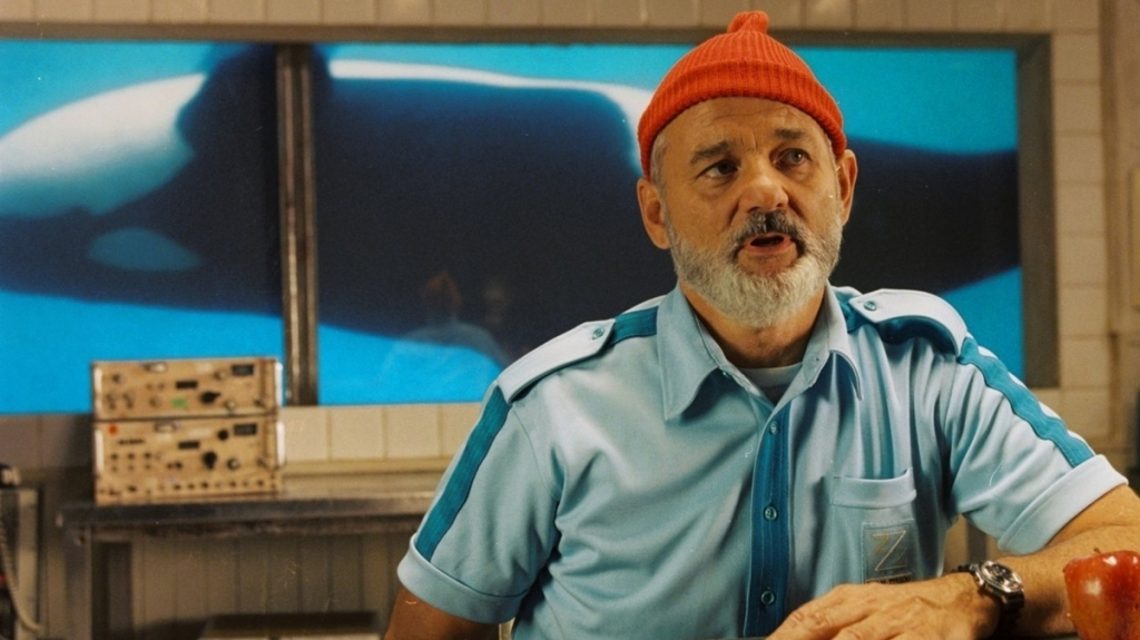 Screen capture from The Life Aquatic with Steve Zissou. A man (Bill Murray) stands in ship's cabin with an orca visible through the window in the background.