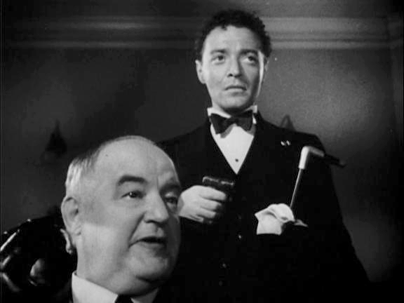 Joel Cairo [Peter Lorre] is holding a cane and is standing behind Kasper Gutman [Sydney Greenstreet]. Both are looking off screen and wear stern and displeased expressions