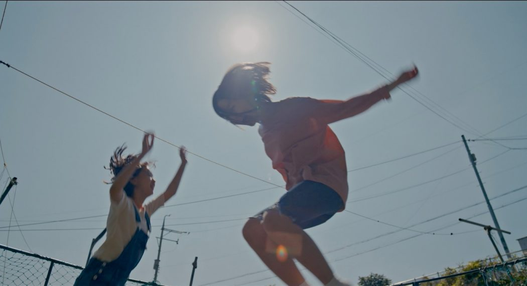 The image is from House of Hummingbird. Two girls jump and play on a summer day.