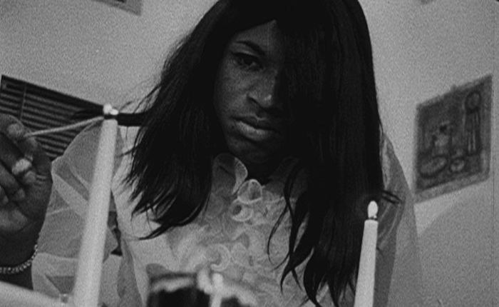 An unnamed Black woman stands above the camera, wearing a neutral expression. She wears a white frilly blouse and is lighting a pair of thin white candles