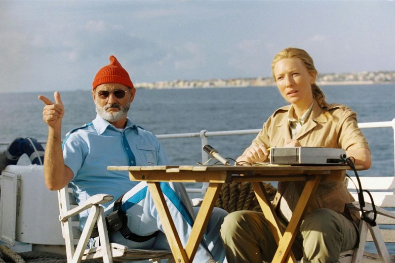 Screen capture from The Life Aquatic with Steve Zissou. A man (Bill Murray) and a woman (Cate Blanchett) sit at a table with a dictaphone on it aboard a boat.
