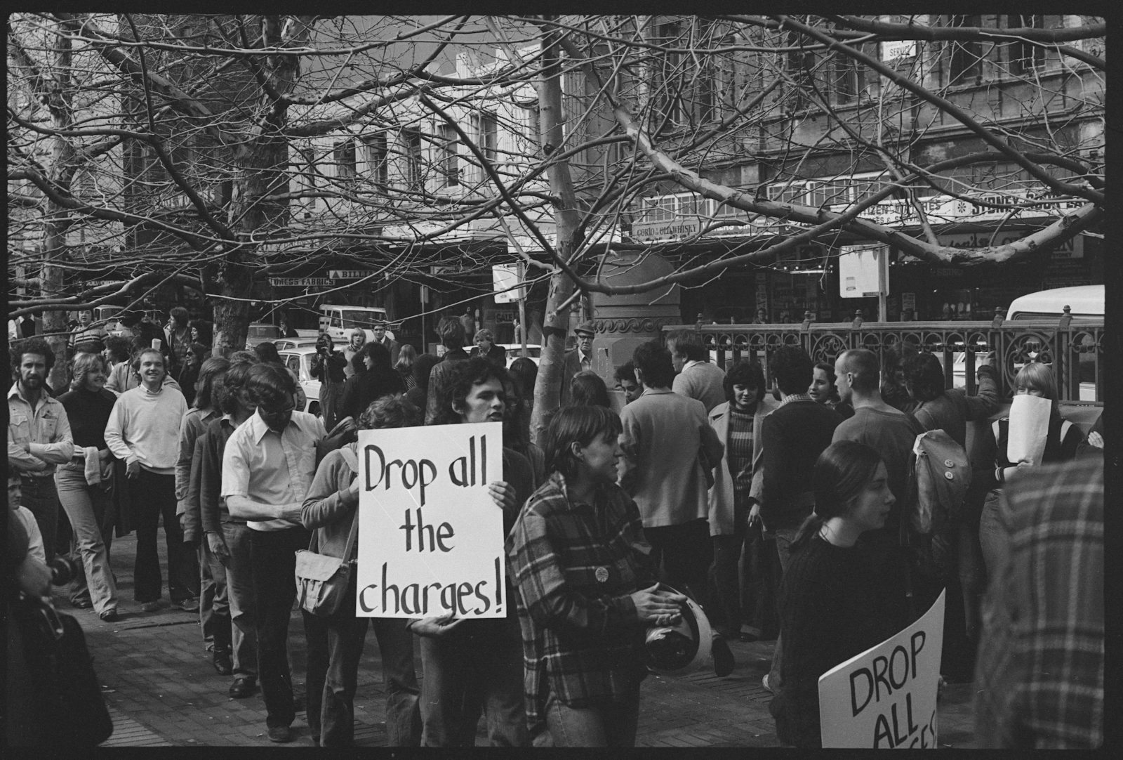 """A Gay Liberation protest in New South Wales circa 1967. A man in the foreground is holding a white sign with black text that reads """"Drop all the charges!"""