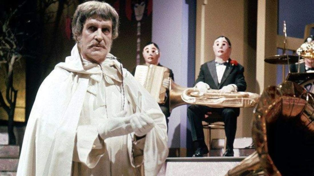 Vincent Price as Dr Phibes, left of screen in white robes, with a robot band behind him.