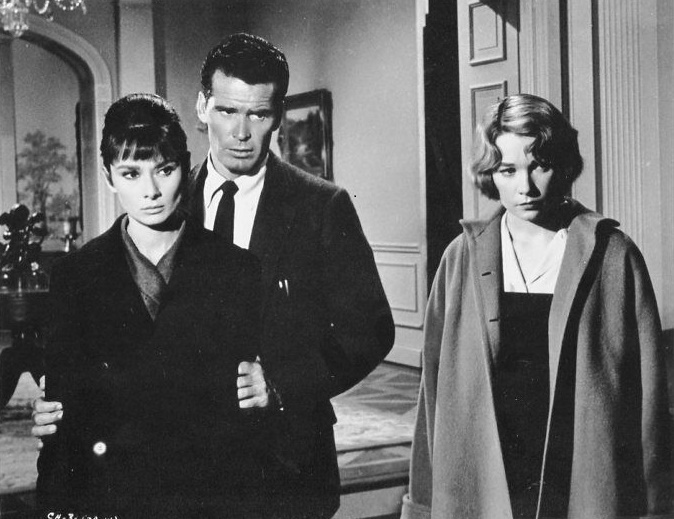 Dr. Joe Cardin [James Garner] stands behind Karen Wright [Audrey Hepburn], holding her firmly by her upper arms. Martha Dobie [Shirley MacLaine] stands to their left. All three have firm and displeased expressions.