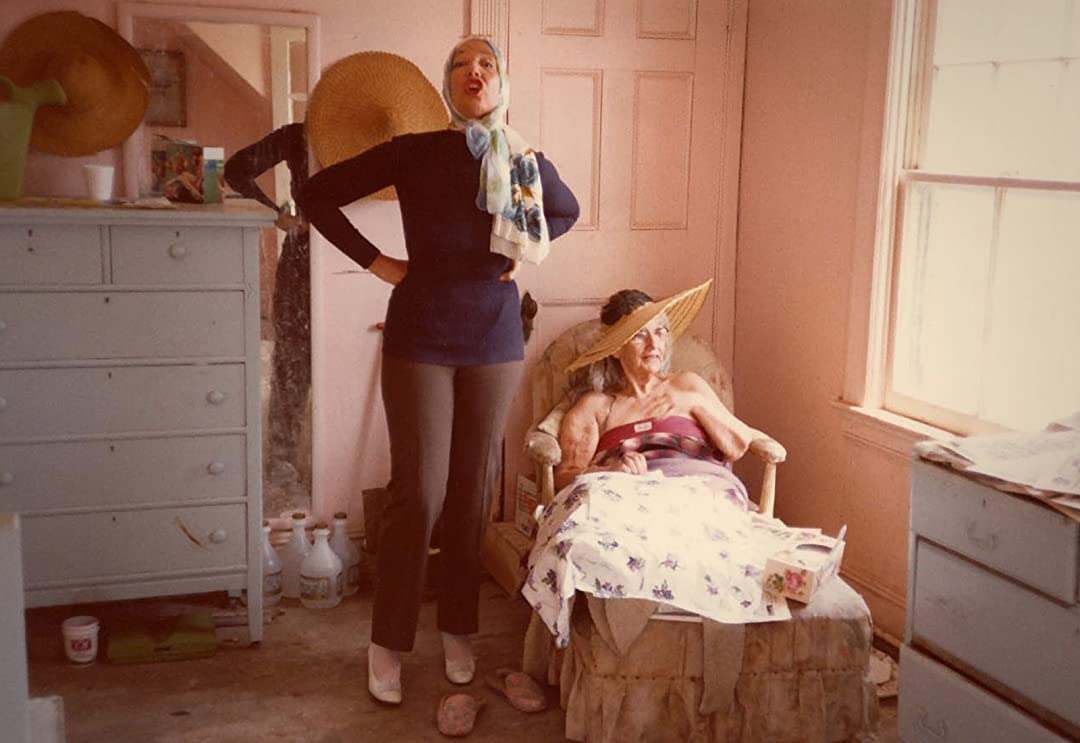 This image is from Grey Gardens (1975). Big Edie sits in her bed and looks out of the window whilst Little Edit shouts in the direction of the camera.