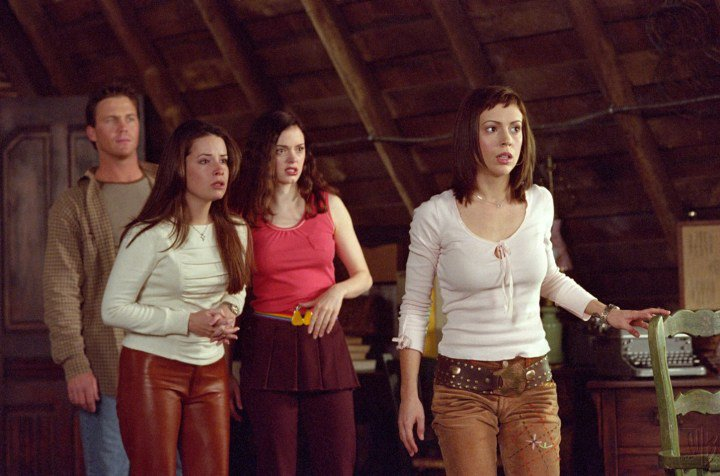 This image is from the TV Show Charmed. Leo, Piper, Paige, and Phoebe are in the Halliwell Manor attic worriedly looking across the room.