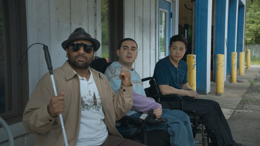 This is a still from the film Come As You Are. A man with a white cane and sunglasses, and two men in wheelchairs are sitting outside a building.