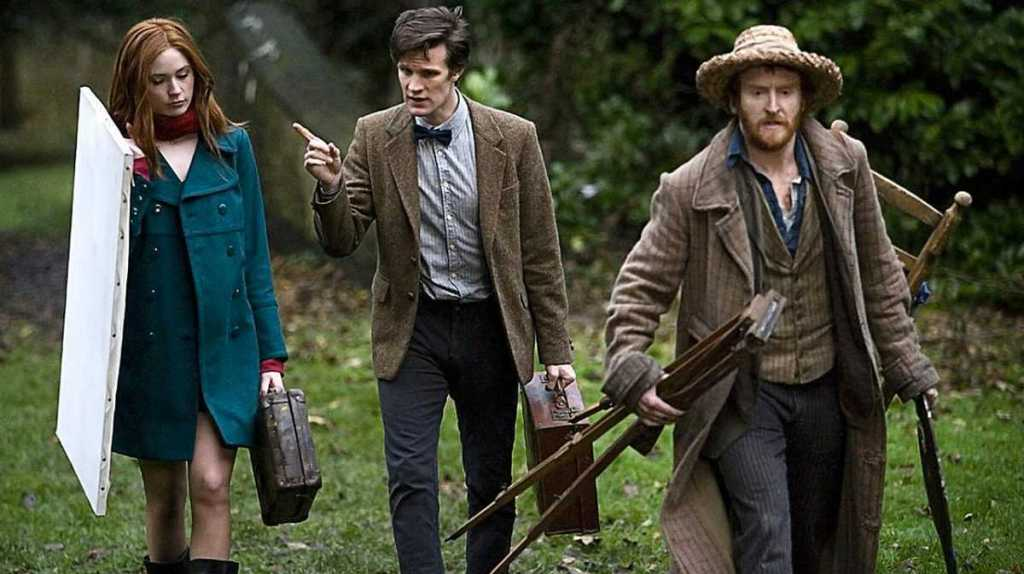 Amy and Vincent walk across wet autumnal grass with painting equipment in hand and The Doctor in between