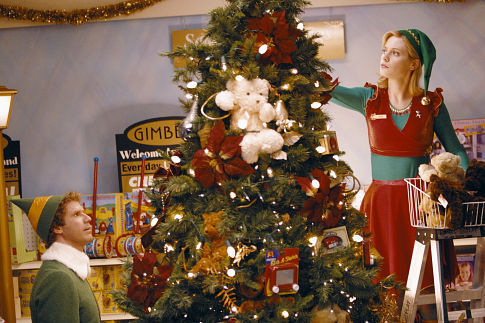 a blonde woman in an elf costume decorates a large Christmas tree while a man in an elf costume looks at her
