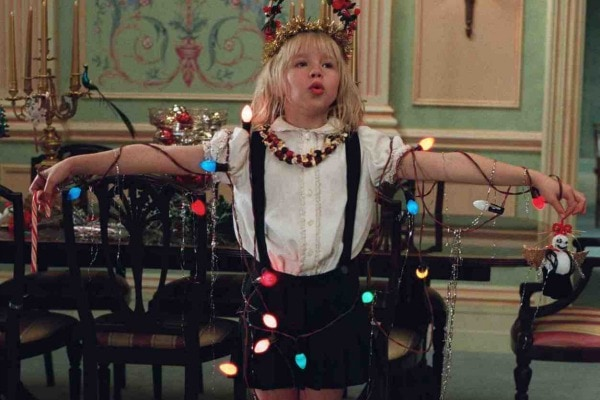 Eloise stands with her arms held out with colorful string lights wrapped around her