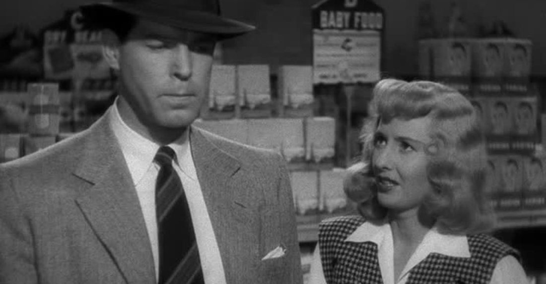 Fred MacMurray as Walter Neff (left) stands in the supermarket in a fedora hat and suit, whilst Barbara Stanwyck as Phyllis Dietrichson looks on worriedly.