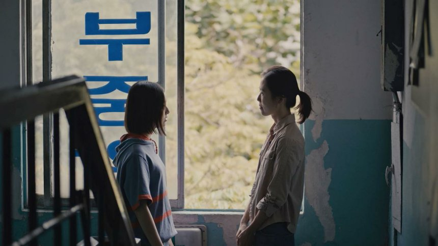 A casually dressed Eunhee and her teacher stand on a dilapidated stairwell looking at each other earnestly, verdant trees visible outside the window.