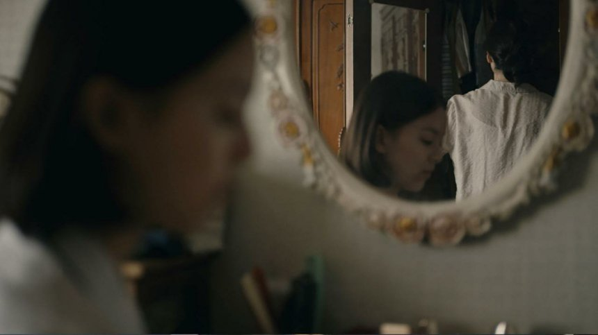 Eunhee is out of focus and sitting thoughtfully. She and her mother are reflected in a mirror, the latter obliviously searching a wardrobe.