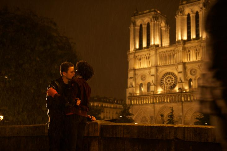 Screenshot from In Her Hands. A man and a woman embrace outside of Notre Dame at night.