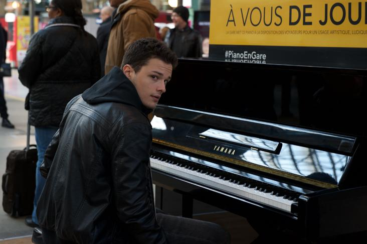 Screenshot from In Her Hands. A man sits at a piano in a train station.
