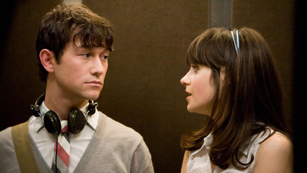 This image is from (500) Days of Summer. Tom and Summer stand in a lift and are engaging in conversation.