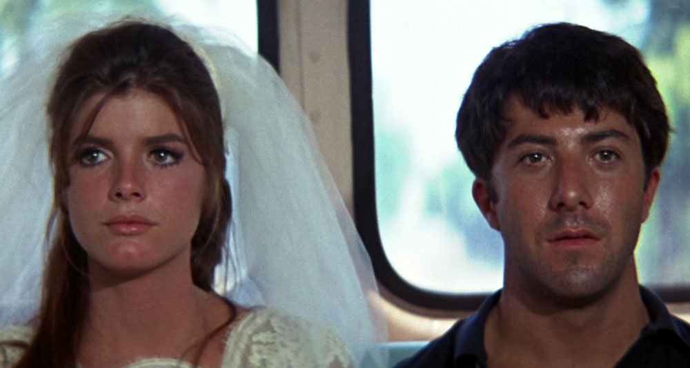 This image is from The Graduate. A man and women sit site by side. The woman is in a wedding dress.
