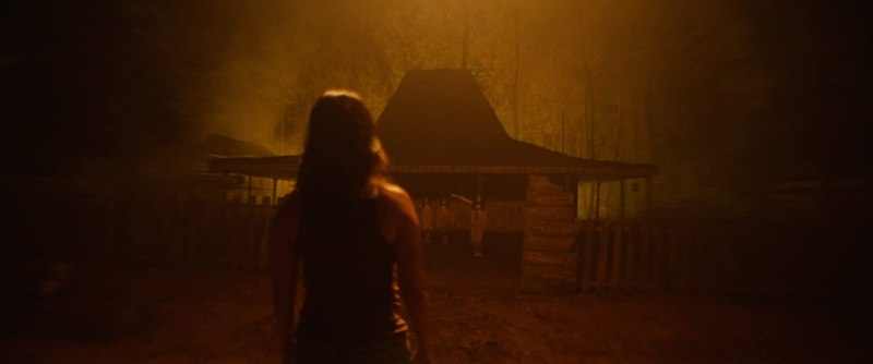 Image still from the horror film Impetigore. Tara Basro staring at an ominous building within yellow mist.