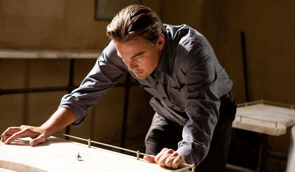 Leonardo DiCaprio in a scene from the film 'Inception.' His character is hunched over, watching a top as it spins.