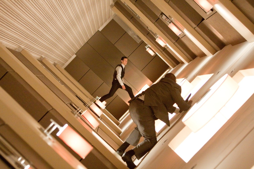 Joseph Gordon-Levitt in a scene from the film 'Inception.' His character is wearing a suit while in a rotating hallway, while a man on the wall watches.